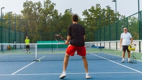 Het trainen of het onderwijzen speltennis op een hof openlucht Opleiding van professionele sportenspelers stock videobeelden