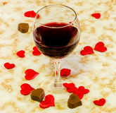 Het transparante glas met rode wijn, hartchocolade en textiel rode valentijnskaartharten, oude document achtergrond, sluit omhoog Royalty-vrije Stock Foto