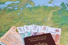 Het treinkaartje, het geld en het Russische paspoort liggen op een kaart van Rusland Stock Fotografie