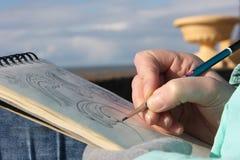 Het trekken in een notitieboekje op de waterkant Royalty-vrije Stock Foto's