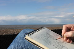 Het trekken in een notitieboekje op de waterkant Stock Afbeelding