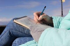 Het trekken in een notitieboekje op de waterkant Royalty-vrije Stock Foto