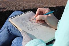 Het trekken in een notitieboekje op de waterkant Stock Foto's
