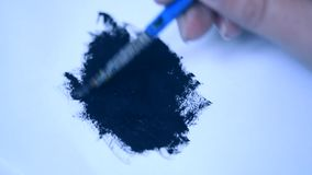 Het trekken met een borstel op Witboek met zwarte olieverf stock footage
