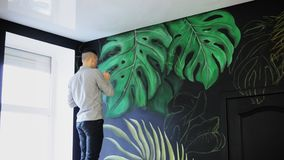 Het trekken op de muur Graffitikunstenaar met borstel Trek groene tak stock footage
