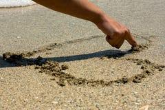 Het trekken van een hart in zand Stock Foto