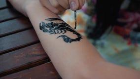 Het trekken van een kind` s tatoegering op zijn hand met zwarte verf Het mooie trekken op een kinderen` s hand stock videobeelden