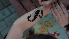 Het trekken van een kind` s tatoegering op zijn hand met zwarte verf Het mooie trekken op een kinderen` s hand stock video