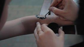 Het trekken van een kind` s tatoegering op zijn hand met zwarte verf Het mooie trekken op een kinderen` s hand stock footage