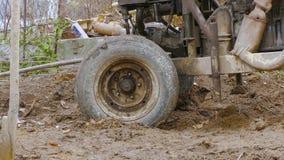 Het trekken van een roestige geïmproviseerde installatie uit modder stock videobeelden