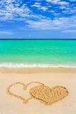 Het trekken van verbonden harten op strand Stock Foto's
