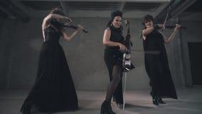 Het trio van Nice van violistmeisjes Een prachtig instrumentaal trio Meisjes in zwarte stock footage
