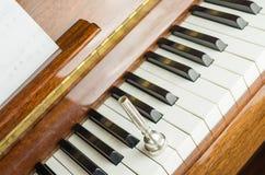 het trompetmondstuk op de pianosleutels, sluit omhoog Stock Afbeeldingen