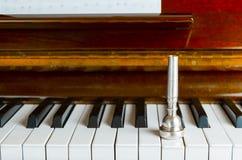het trompetmondstuk op de pianosleutels, sluit omhoog Stock Foto's
