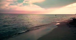 Het tropische Caraïbische strandoverzees met gouden zand bij zonsondergang, kleurrijk van hemel met langzame overzeese beweging,  stock videobeelden