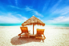Het tropische strand met met stro bedekt paraplu en stoelen voor ontspanning Royalty-vrije Stock Fotografie