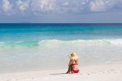 Het tropische strand, turquise water en horizon De slanke blondevrouw zit in rood zwempak Royalty-vrije Stock Foto's