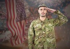 Het trotse militair groeten tegen fladderend Amerikaans vlag en vuurwerk op achtergrond Royalty-vrije Stock Foto's