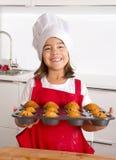 Het trotse vrouwelijke kind die haar zelf gemaakte muffin voorstellen koekt het leren baksel dragend rode schort en kookt hoed ge Royalty-vrije Stock Afbeelding