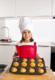 Het trotse vrouwelijke kind die haar zelf gemaakte muffin voorstellen koekt het leren baksel dragend rode schort en kookt hoed ge Stock Foto