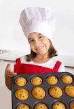Het trotse vrouwelijke kind die haar zelf gemaakte muffin voorstellen koekt het leren baksel dragend rode schort en kookt hoed ge Royalty-vrije Stock Fotografie