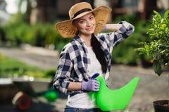 Het tuinieren concept Portret van mooie vrouwelijke tuinman het water geven installaties in de tuin in hete de zomerdag stock foto