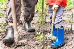 Het tuinieren De benen van vrouw en kind is op de grond met het tuinieren Royalty-vrije Stock Foto