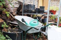 Het tuinieren materiaal: kar, gieter, kratten, meststoffen en bloemen stock fotografie