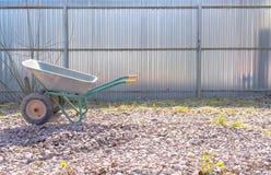 Het tuinieren nieuwe hulpmiddelen, rietdienblad Ijzerkruiwagen op het puin stock foto's