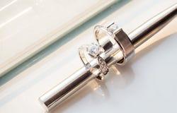 het tussenvoegsel van het metaaleetstokje binnen twee diamanten bruiloftringen voor bruidegom en bruid op witte achtergrond stock foto