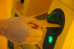 Het tussenvoegselkaart van de mensenhand aan gele geautomatiseerde tellermachine ATM Royalty-vrije Stock Foto's