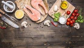 Het twee zalmlapje vlees op papier met peper, de kruiden, een mes en een vork, boter, kruiden, kersentomaten op houten rustieke b Stock Afbeelding