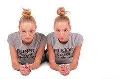 Het tweeling sportmeisjes liggen Stock Afbeeldingen