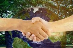Het tweepersoonshand schudden met aardeachtergrond royalty-vrije stock foto