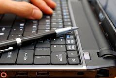 Het typen van de hand op laptop met pen Stock Afbeeldingen