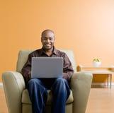 Het typen van de mens op laptop in woonkamer stock fotografie