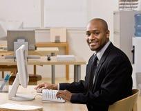 Het typen van de zakenman op computer bij bureau stock foto