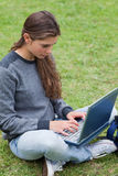 Het typen van het meisje op haar laptop terwijl het bekijken scr Stock Fotografie