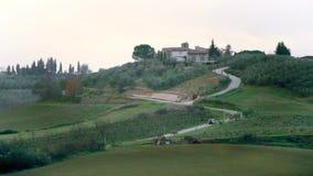 Het typische landschap van Toscanië met auto die op de weg in de groene heuvels reizen stock footage