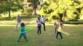Het uitgebreide familie spelen met hulahoepels stock video