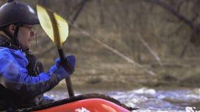 Het uitgeruste kayaker roeien tegen de stroom stock videobeelden