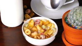 Het uithollen van en het eten van graangewassencornflakes en froot lijnen van een witte kom stock video