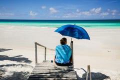Het uitnodigen mening van strand en rustige, turkooise oceaan met vrouwenzitting in voorgrond, holdingsparaplu Stock Foto