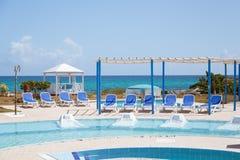 Het uitnodigen van verbazende schitterende mening van openluchtkuuroord zwembad en gronden tegen rustige oceaanachtergrond Royalty-vrije Stock Afbeeldingen