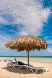 Het uitnodigen zitkamerstoelen onder tropische paraplu op het strand stock fotografie