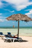 Het uitnodigen zitkamerstoelen onder tropische paraplu op het strand, sai stock fotografie