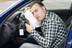 Het uitputten van de mens slaapt in een auto. Stock Foto's
