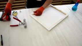 het uitrekken van het canvas op het houten kader van het beeld stock videobeelden