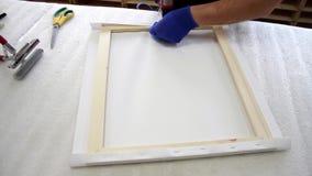 Het uitrekken van het canvas op houten stock footage