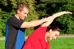 Het uitrekken van de vrouw zich met persoonlijke trainer in openlucht Royalty-vrije Stock Fotografie